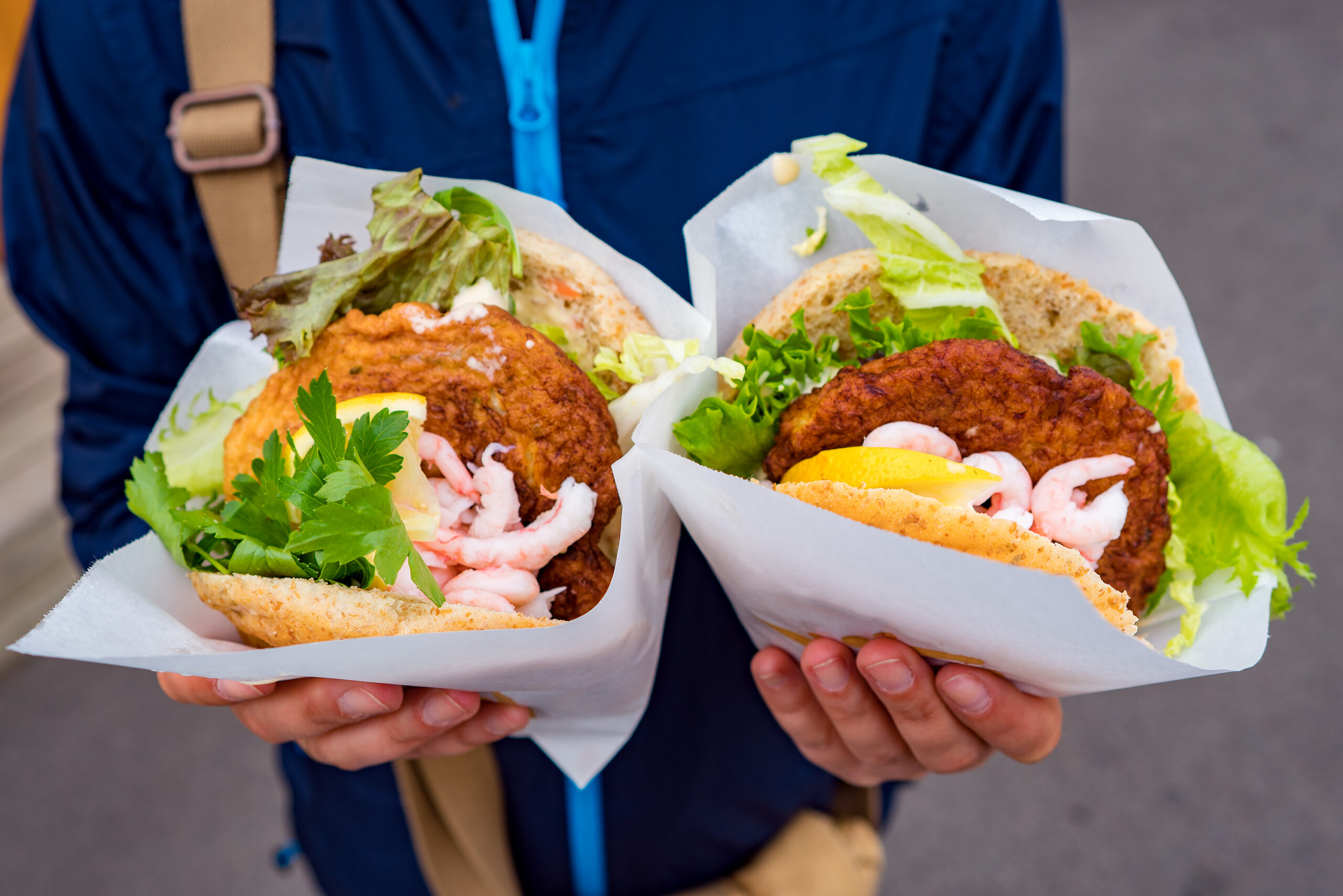 Fast street food seafood. Norway Lofoten Islands, fish cutlet with salad and grilled shrimp